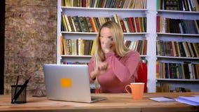 Портрет сконцентрированной кавказской девушки с прошивкой сытно работая с ноутбуком на предпосылке книжных полка видеоматериал