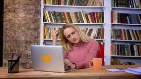 Портрет сконцентрированной кавказской девушки с прошивкой внимательно работая с ноутбуком на предпосылке книжных полка акции видеоматериалы