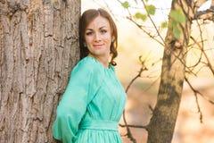 Портрет склонности девушки на дереве в древесинах Стоковые Изображения