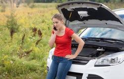Портрет склонности женщины на сломленном автомобиле с открытыми клобуком и talki Стоковые Фотографии RF