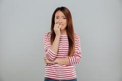 Портрет слабонервной азиатской девушки сдерживая ее ногти стоковые фото