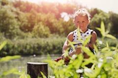 Портрет сладостной маленькой счастливой девушки пока сидящ рекой Стоковые Изображения RF
