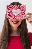 Портрет сладостной совершенной девушки усмехаясь на камере с сердцем сформировал бумагу в ее руках День ` s дня или женщин ` s ва Стоковые Изображения RF