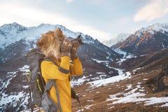 Портрет сладостной туристской девушки в большой меховой шапке фотографирует на ее цифровой фотокамера в горах Стоковое Изображение RF