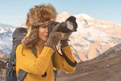 Портрет сладостной туристской девушки в большой меховой шапке фотографирует на ее цифровой фотокамера в горах Стоковая Фотография RF