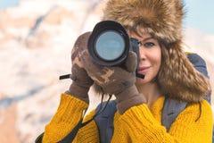 Портрет сладостной туристской девушки в большой меховой шапке фотографирует на ее цифровой фотокамера в горах Стоковая Фотография