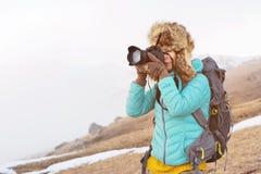 Портрет сладостной туристской девушки в большой меховой шапке фотографирует на ее цифровой фотокамера в горах Стоковые Фотографии RF