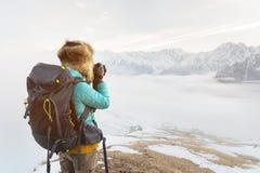 Портрет сладостной туристской девушки в большой меховой шапке фотографирует на ее цифровой фотокамера в горах Стоковые Изображения RF