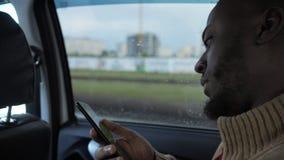 Портрет смартфона просматривать чернокожего человека едет автомобиль в дождливом дне в городе акции видеоматериалы