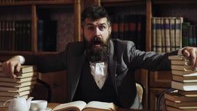 Портрет смешного бородатого человека с много книг внутри в библиотеке Студент болвана смешной подготавливая для экзаменов универс видеоматериал