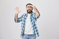 Портрет смешного обычного европейского человека смотря далеко с рукой на лбе пока говорить высокий с жестом и усмехаться стоковые фотографии rf