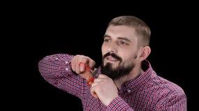 Портрет смешного человека режа его бороды с ножницами над bl стоковые изображения rf