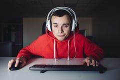 Портрет смешного gamer играет игры на его компьютере Молодой gamer использует ваш компьютер Молодой человек использует компьютер стоковое фото