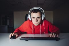 Портрет смешного gamer смотря тщательно контролирует ваш компьютер и видеоигры играть стоковые изображения