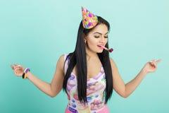 Портрет смешной женщины в шляпе дня рождения и розовой рубашке на голубой предпосылке Торжество и партия потеха отца ребенка имея стоковые фото