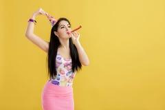 Портрет смешной женщины в шляпе дня рождения и розовой рубашке на желтой предпосылке Торжество и партия потеха отца ребенка имея  стоковое изображение