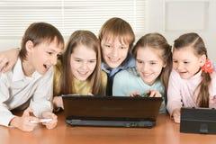 Портрет смешных мальчиков и девушек используя цифровые приборы совместно на таблице дома стоковые изображения