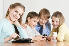 Портрет смешных мальчиков и девушек используя цифровые приборы совместно на таблице дома стоковые фотографии rf