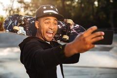 Портрет смеясь над африканского мужского подростка принимая selfie Стоковые Фото