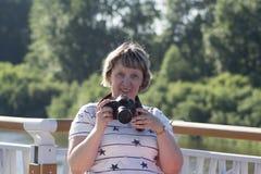 Портрет смеясь над женщины с камерой Стоковая Фотография