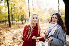 Портрет 2 смеясь над женщин говоря outdoors в парке осени Стоковые Изображения