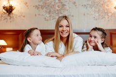 Портрет смеясь над матери и ее двойных детей лежа на b Стоковые Изображения