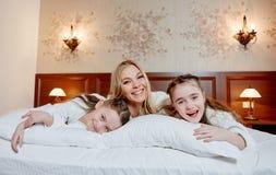 Портрет смеясь над матери и ее двойных детей лежа на b Стоковое Изображение RF