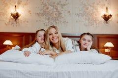 Портрет смеясь над матери и ее двойных детей лежа на b Стоковое фото RF