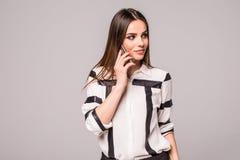Портрет смеясь над привлекательной беседы молодой женщины на мобильном телефоне смеясь над на камере над серым цветом Стоковые Фотографии RF