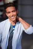 Портрет смеясь над красивого человека касаясь его шеи снаружи Стоковая Фотография