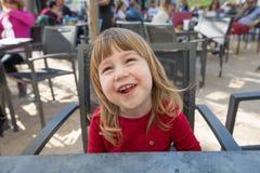Портрет смеясь над ребенка сидя в внешнем баре Стоковое Изображение