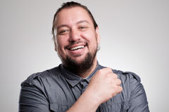Портрет смеяться над молодым человеком против серой стены усмехаться ванты счастливый Стоковое фото RF