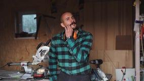 Портрет смелейшего плотника работника с винтажным усиком в рабочей одежде перед инструментами верстака сток-видео