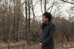 Портрет смотреть молодого красивого человека унылый к левой стороне в парке, древесинах в осени или весне Портрет на природе Стоковые Изображения RF