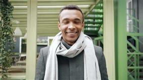 Портрет снятый красивого усмехаясь Афро-американского человека который носит пальто и шарф Handheld портрет замедленного движения сток-видео