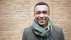 Портрет снятый красивого усмехаясь и подмигивая Афро-американского человека в пальто и шарфе Handheld съемка замедленного движени акции видеоматериалы