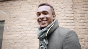 Портрет снятый красивый усмехаться, подмигивать и говорить да Афро-американскому человеку в пальто и шарфе Handheld замедляйте сток-видео