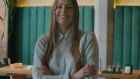 Портрет снятый привлекательной женщины смотря камеру и усмехаясь в городском офисе r акции видеоматериалы