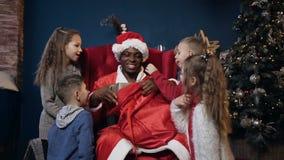 Портрет снятый усмехаясь Санта Клауса давая подарок для детей видеоматериал
