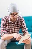 Портрет современного бизнесмена сидя в софе и смотря цифровой планшет стоковая фотография rf