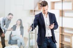 Портрет современного бизнесмена с умной дверью офиса отверстия телефона стоковая фотография rf