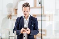 Портрет современного бизнесмена с умным положением телефона в современном офисе стоковое фото rf