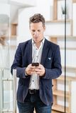 Портрет современного бизнесмена с умным положением телефона в современном офисе стоковые изображения