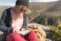Портрет солнечных очков девушки битника нося и шляпы сидя на утесе внешнем в горах против голубого неба Стоковые Фото