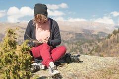 Портрет солнечных очков девушки битника нося и шляпы сидя на утесе внешнем в горах против голубого неба Стоковые Изображения