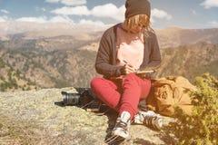 Портрет солнечных очков девушки битника нося и шляпы сидя на утесе внешнем в горах против голубого неба Стоковое Изображение RF