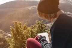 Портрет солнечных очков девушки битника нося и шляпы сидя на утесе внешнем в горах против голубого неба Стоковое Фото