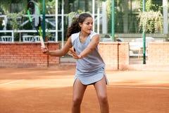 Портрет солнца волос брюнет шарика ракетки девушки суда тренировки девушки теннисиста подростка длинный учит зеленый зеленый цвет Стоковое Изображение