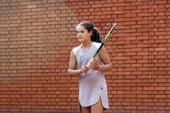 Портрет солнца волос брюнет шарика ракетки девушки суда тренировки девушки теннисиста подростка длинный учит зеленый зеленый цвет Стоковое фото RF