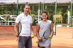 Портрет солнца волос брюнет шарика ракетки девушки суда тренировки девушки теннисиста подростка длинный учит зеленого тренера тре Стоковое Изображение RF